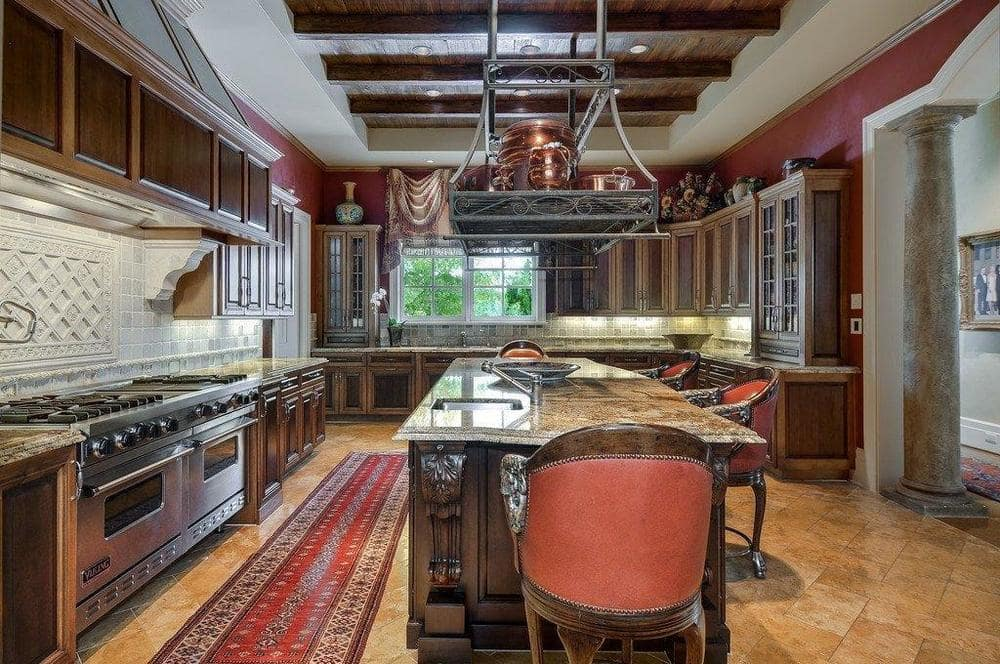 This is the kitchen that has a large dark wooden kitchen island in the middle topped with a wrought-iron pot rack. Image courtesy of Toptenrealestatedeals.com.