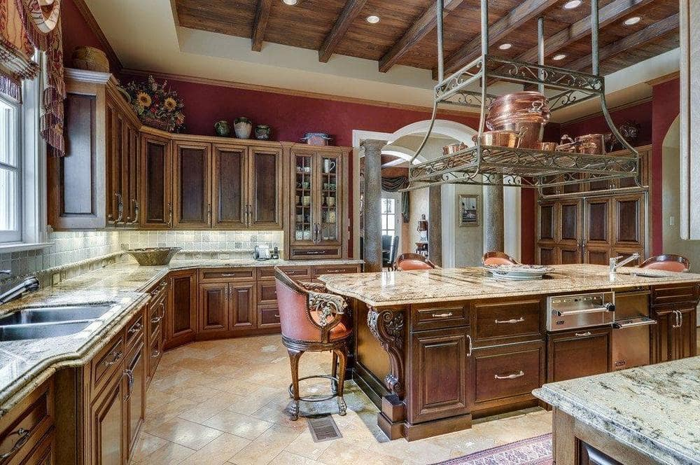 This other view of the kitchen shows more of the surrounding cabinetry that has a dark brown hue matching with the wooden tray ceiling and kitchen island. Image courtesy of Toptenrealestatedeals.com.