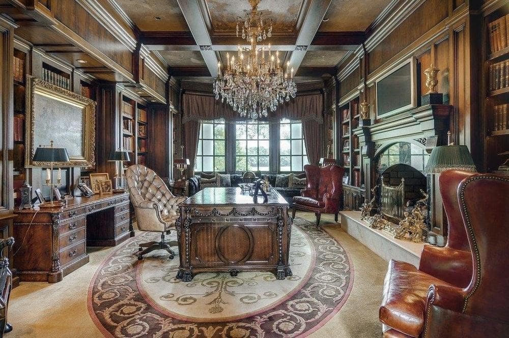 This is the home office with a large ornately-carved desk topped with a large crystal chandelier hanging from the coffered ceiling. Image courtesy of Toptenrealestatedeals.com.