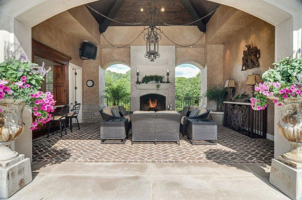 This is a closer look at the covered patio at the edge of the swimming pool. This area is warmed by a fireplace across from the sofa set. Image courtesy of Toptenrealestatedeals.com.