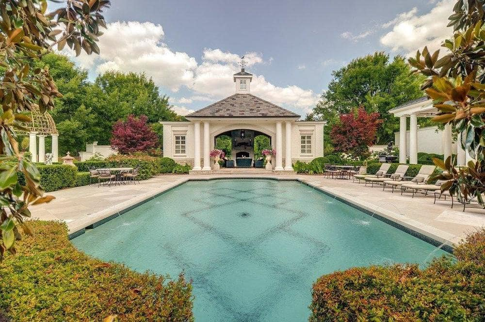 This is the pool with a structure at the far edge with a covered patio and a row of lawn chairs on the side to better enjoy the poolside area. Image courtesy of Toptenrealestatedeals.com.