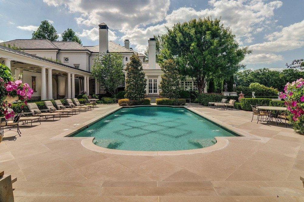 This is another look at the swimming pool showcasing the landscaping of shrubs and tall trees at the far edge that complements the bright exterior walls and windows of the house. Image courtesy of Toptenrealestatedeals.com.