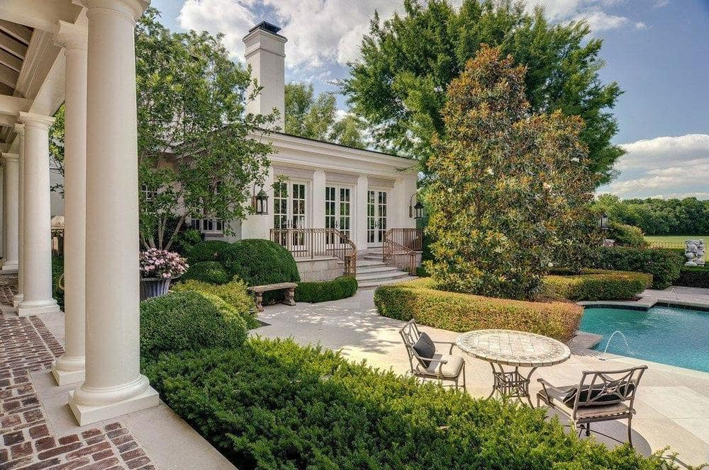 This is a look at the edge of the poolside area with various outdoor sitting areas adorned with hedges of shrubs and tall trees. Image courtesy of Toptenrealestatedeals.com.