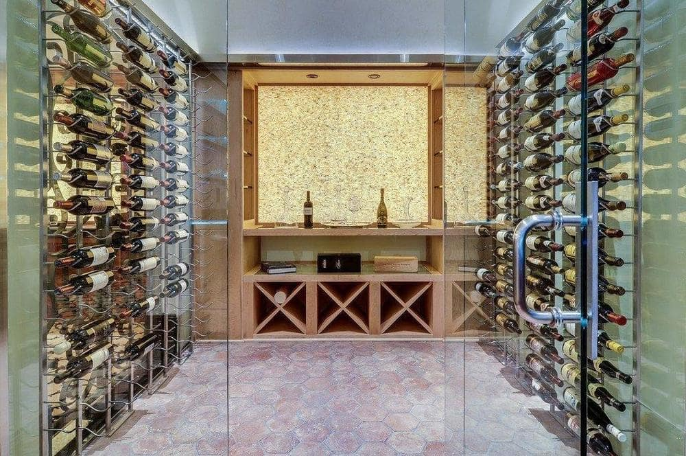This is the wine storage behind the bar. It has a glass door and structures on the walls to store wine bottles. Image courtesy of Toptenrealestatedeals.com.