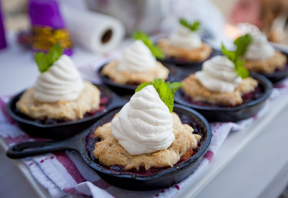 Individual berry cobblers with whipped cream and mint leaves in small cooking skillets.