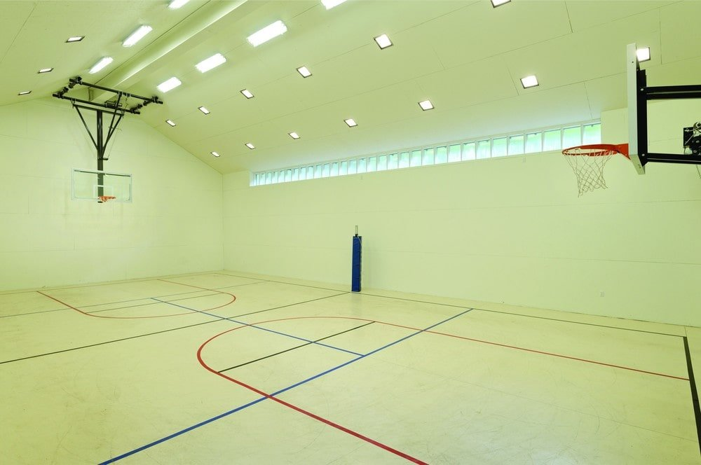 This is the professional-sized indoor basketball court of the property with light green tone to its walls and arched ceiling. Image courtesy of Toptenrealestatedeals.com.