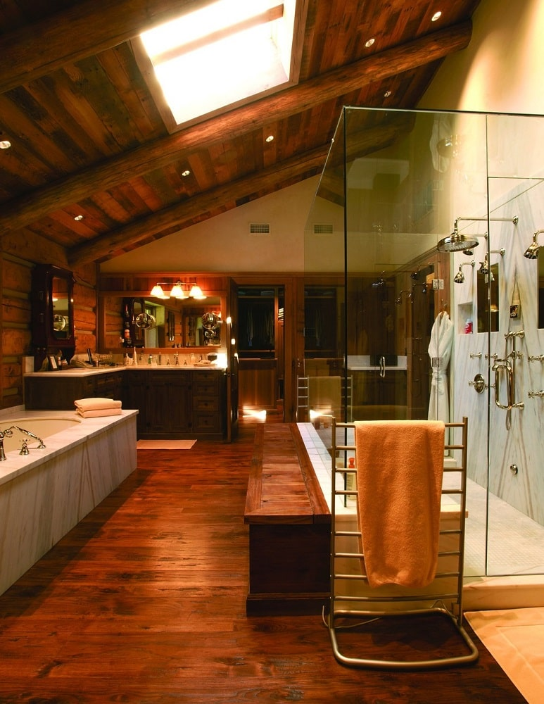 The primary kitchen has a consistent dark wooden tone to its floor, walls and shed ceiling with a skylight above the bathtub and the glass-enclosed shower area. Image courtesy of Toptenrealestatedeals.com.