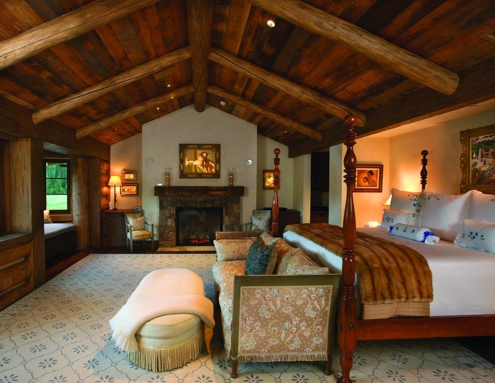 The primary bedroom has a wooden four-poster bed that matches the tone of the cathedral ceiling and the dark hardwood flooring. This also matches the mantle of the fireplace on the far side. Image courtesy of Toptenrealestatedeals.com.