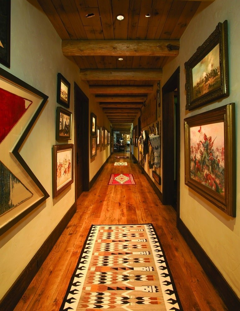 The hallway has hardwood flooring, beige walls and a wooden ceiling. These are then complemented by the various wall-mounted artworks and the colorful patterned area rugs. Image courtesy of Toptenrealestatedeals.com.