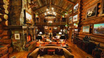 This is a look at the large living room with a tall wooden ceiling, a large stone fireplace and wooden log walls that match the tone of the hardwood flooring. Image courtesy of Toptenrealestatedeals.com.