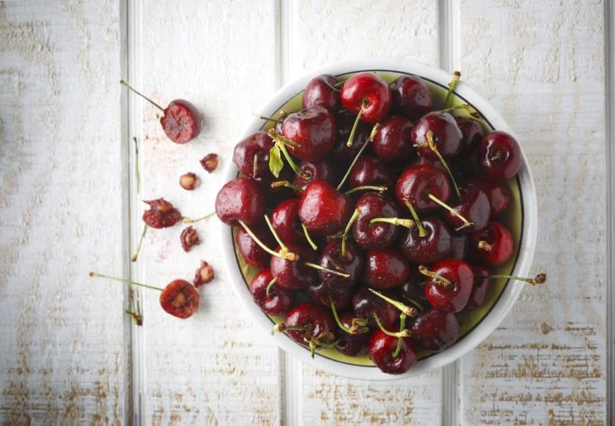 A bowl of Bing cherries on top of a wood plank table.