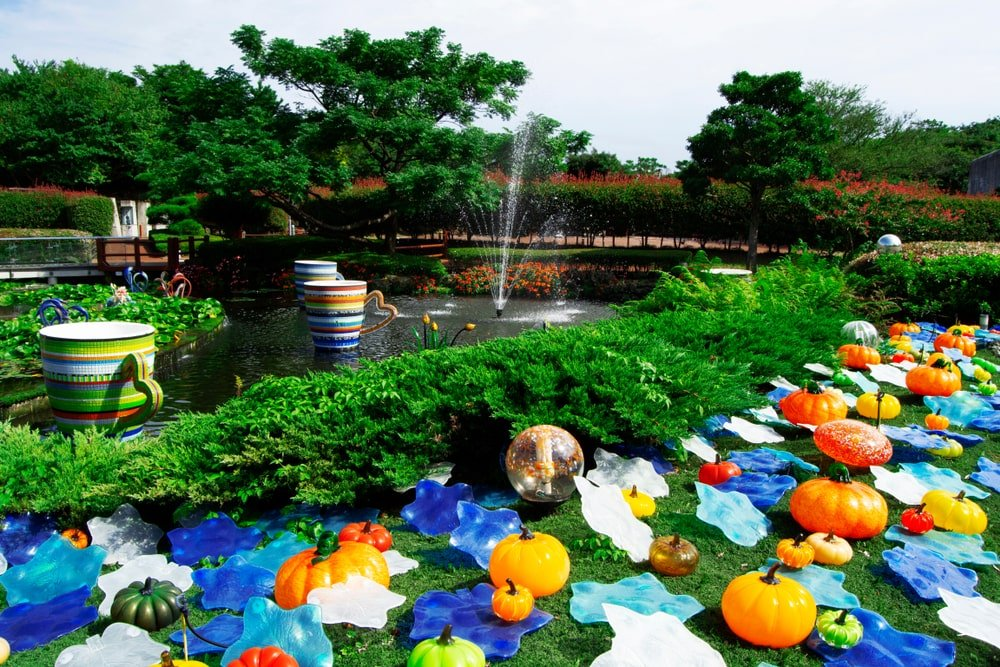 A bunch of glass flowers and pumpkins strewn about the garden in Jeju, South Korea.