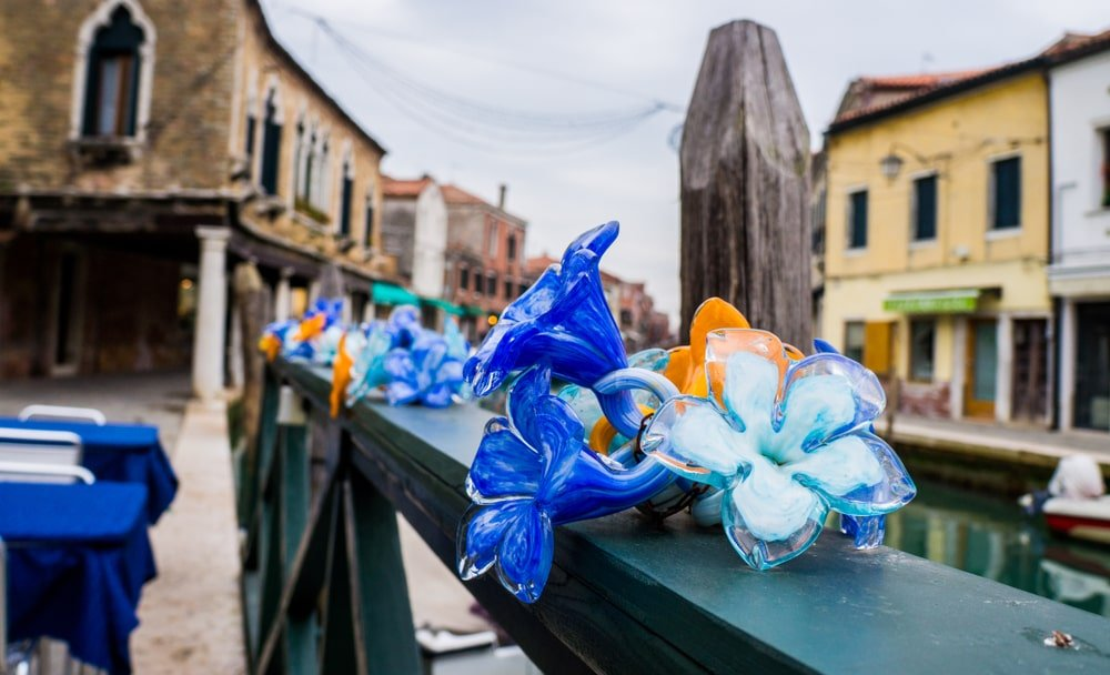 A close look at Murano glass flowers on a rustic bridge in Italy.