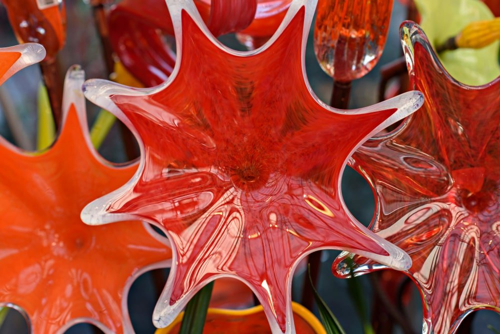 A close look at red and orange blown glass flowers.