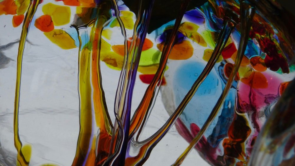 A close look at a glass blown flower with dripping colors.