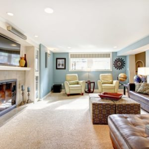 This is a spacious family room with blue walls that contrast the large brown leather sectional sofa across from the TV and fireplace.