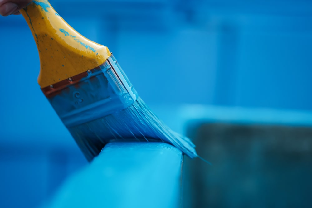 Painting a wooden furniture with blue paint color.