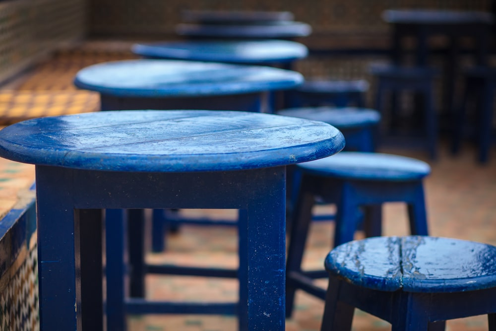 Blue-painted round wooden tables and chairs.