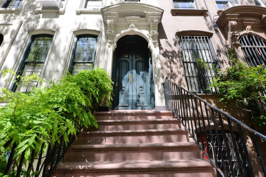 This is the view of the main entrance of the townhome with tall windows, intricate details and terracotta steps adorned by wrought-iron railings and potted plants. Image courtesy of Toptenrealestatedeals.com.