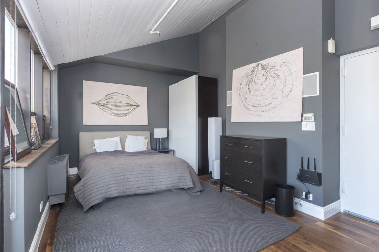 The bedroom has a white shed ceiling contrasted by the gray walls that match well with the gray bed. Image courtesy of Toptenrealestatedeals.com.