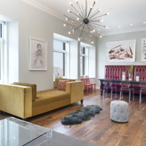 This is a look at a great room of the penthouse with a living room and a dining area on the far side. The living room is adorned with a large decorative lighting. Image courtesy of Toptenrealestatedeals.com.