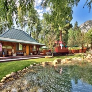 This is a back view of the ranch's main house. Here you can see the wooden exteriors and patios complemented by the landscape that has grass lawns, tall trees and a fishing pond adorned with decorative rocks. Image courtesy of Toptenrealestatedeals.com.