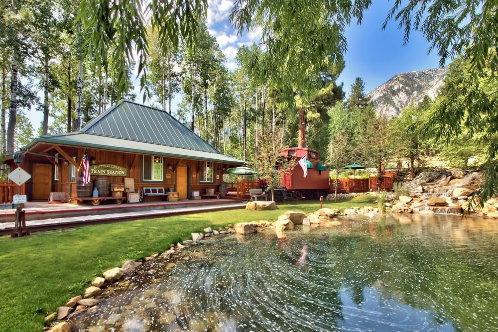 This is a back view of the ranch's main house with a train station look. Here you can see the wooden exteriors and patios complemented by the landscape that has grass lawns, tall trees and a fishing pond adorned with decorative rocks. Image courtesy of Toptenrealestatedeals.com.