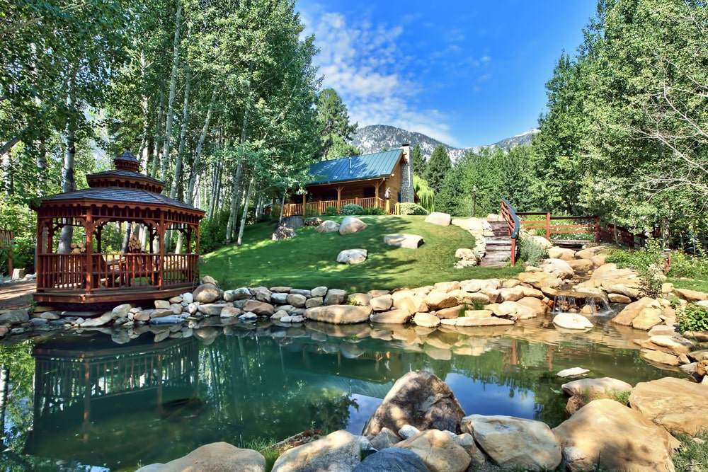 This other pond of the property has a wooden gazebo on the side adorned with the decorative rocks lining the sides of the pond before transitioning to the grass lawn. Image courtesy of Toptenrealestatedeals.com.