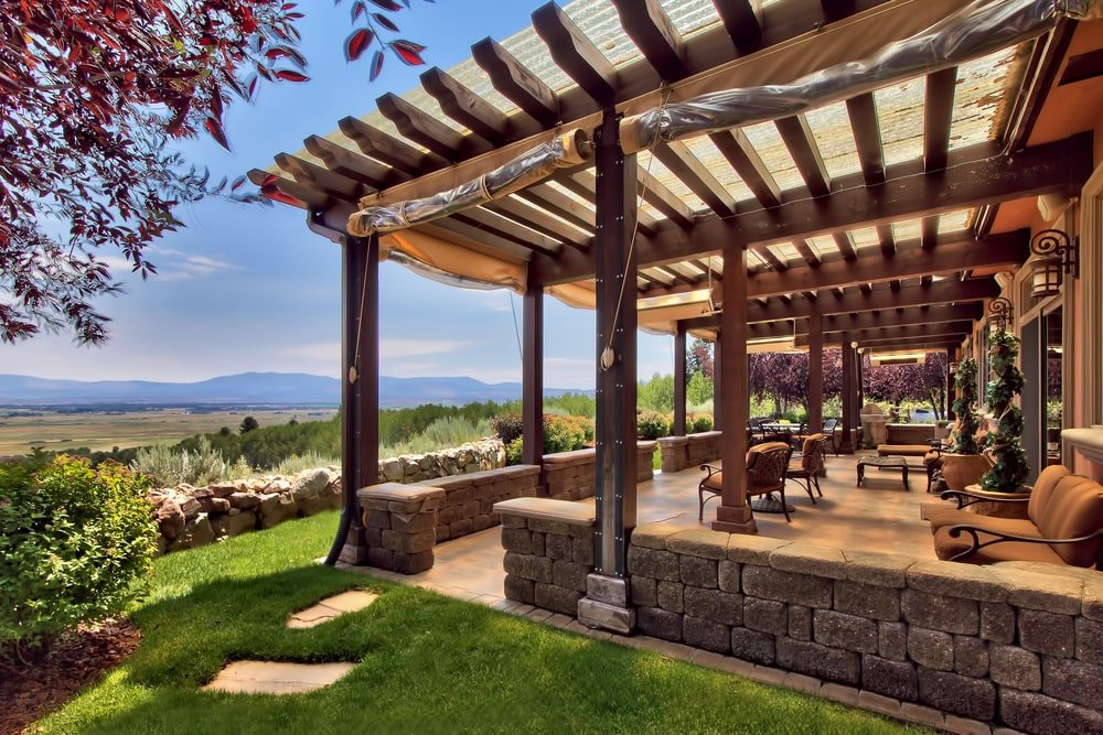 This is a close look at the covered patio at the side of the house with a beamed ceiling, wooden pillars, and various sitting areas facing the sweeping views. Image courtesy of Toptenrealestatedeals.com.