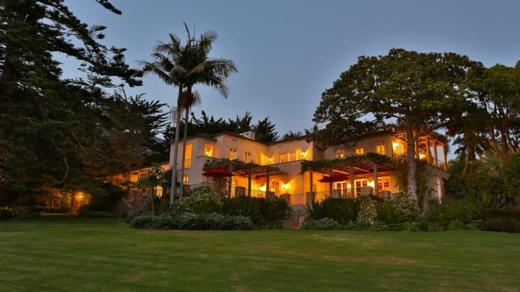 This is a nighttime view of the house with multiple glowing windows and balconies from the interior lights. These are then complemented by the surrounding landscape of tall tropical trees and grass lawn. Image courtesy of Toptenrealestatedeals.com.