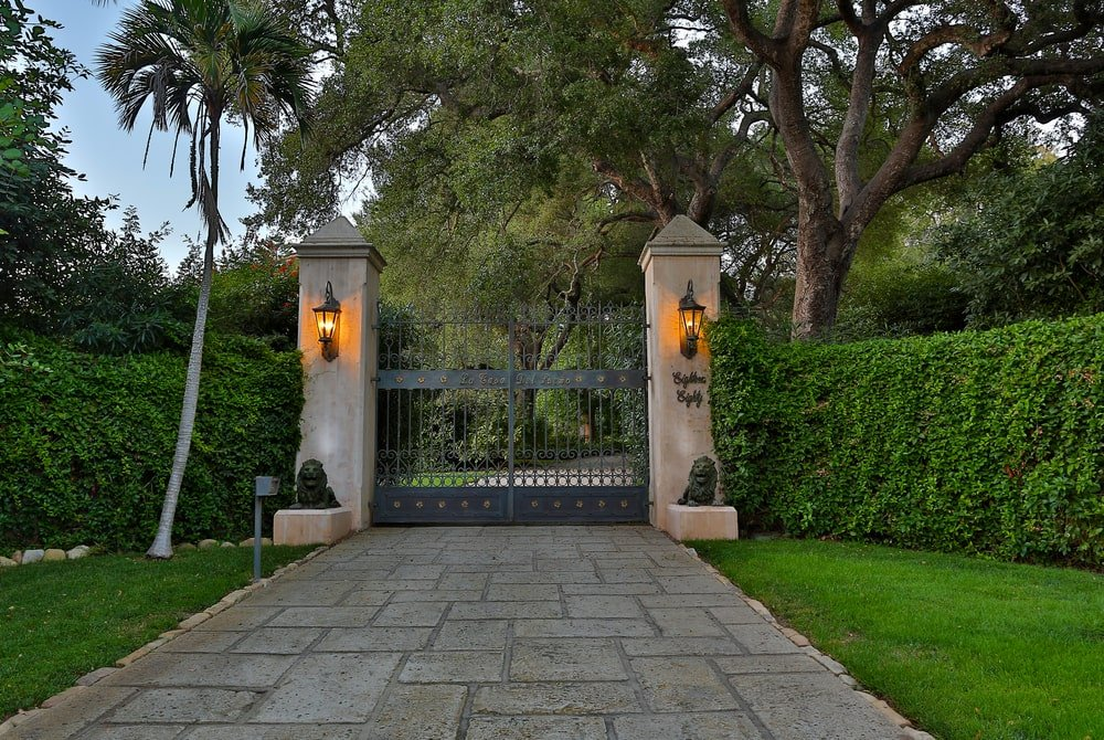 This is the main gate of the estate with two large concrete pillars supporting the wrought-iron gate adorned with outdoor lamps. Image courtesy of Toptenrealestatedeals.com.
