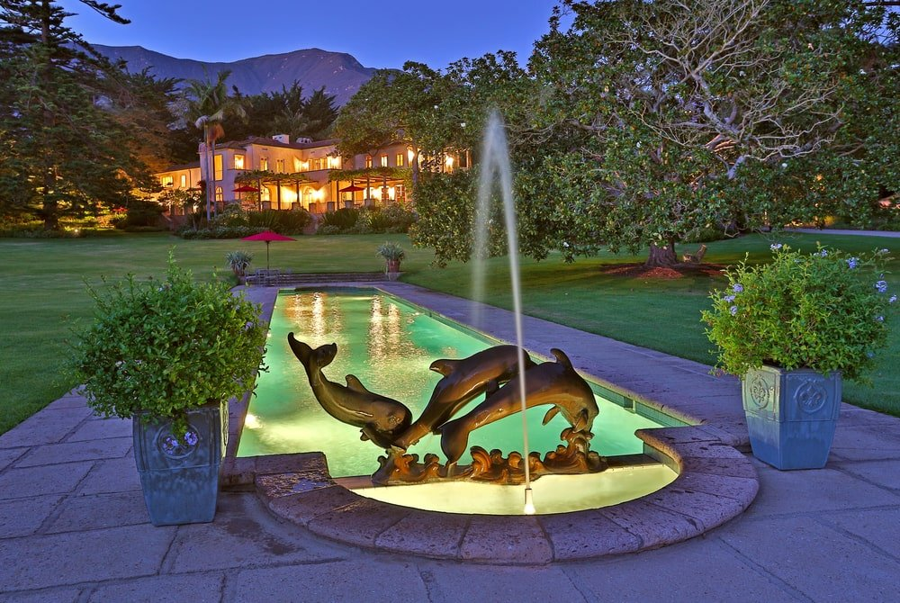 This nighttime look at the pool shows its ethereal glow and decorative dolphin fountain at the edge. Image courtesy of Toptenrealestatedeals.com.