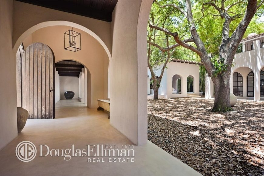 This is a look at the central courtyard of the mansion surrounded by the beige arches and pillars of the exteriors. You can also see here the courtyard is surrounded by hallways. Image courtesy of Toptenrealestatedeals.com.
