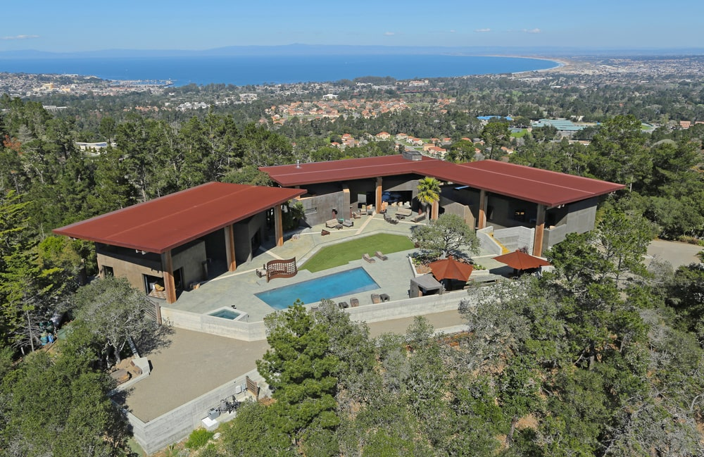 This is an aerial view of the estate. Here you can see the flat roofs of the house with a red tone that contrasts the surrounding green landscape. Image courtesy of Toptenrealestatedeals.com.