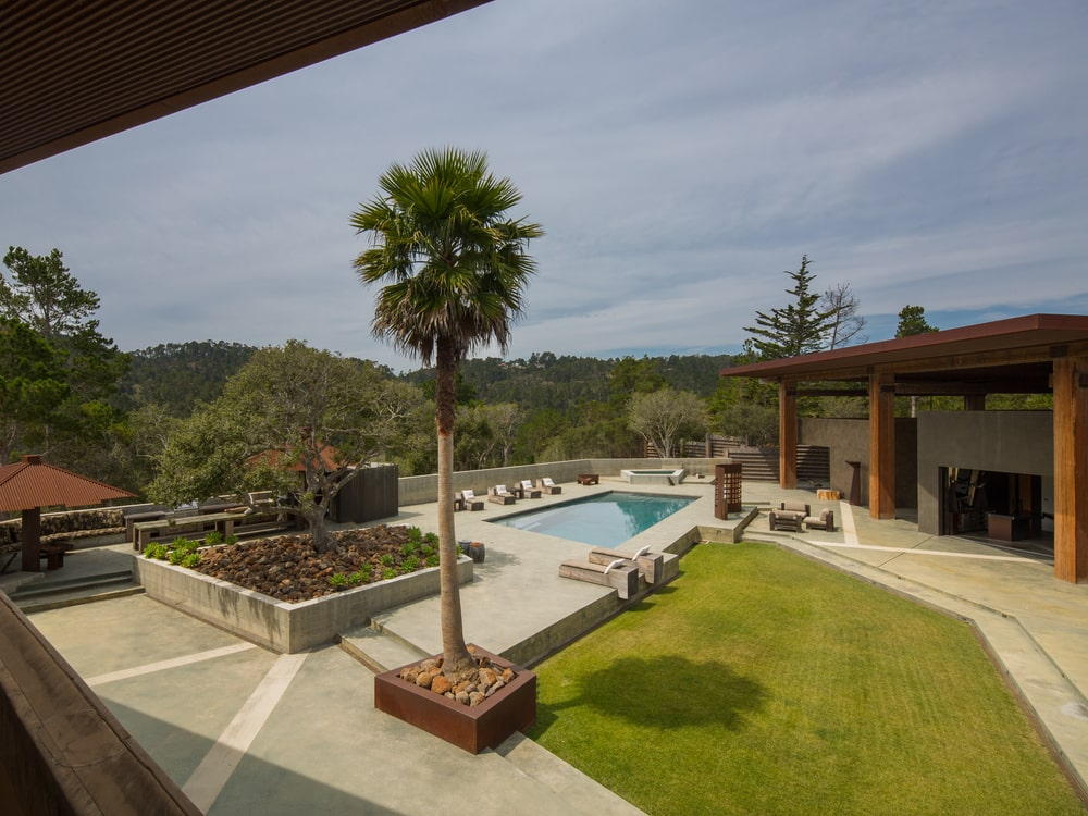 This is a view of the back of the house with a large outdoor area, a pool and a grass lawn beside it. Image courtesy of Toptenrealestatedeals.com.