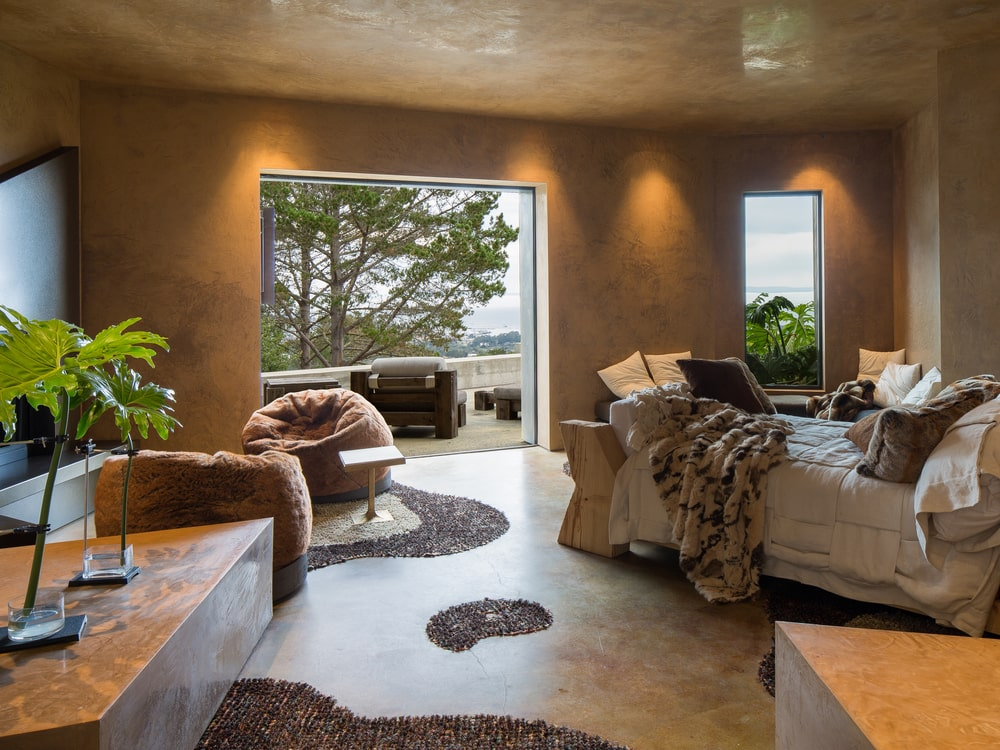 This bedroom has earthy tones to its ceiling and walls that open up to the terrace through a large archway. Image courtesy of Toptenrealestatedeals.com.