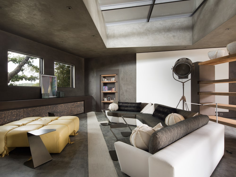 This family room is dominated by the large curved sectional sofa with black cushions. This is contrasted by the bright yellow cushioned coffee table. Image courtesy of Toptenrealestatedeals.com.