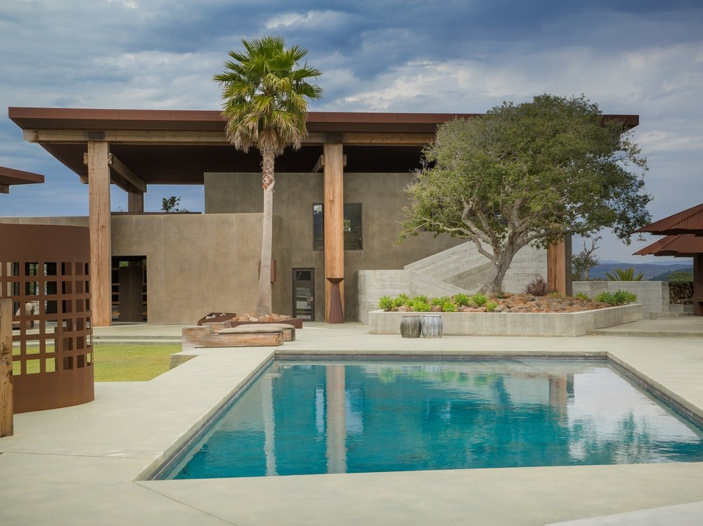 This is a look at the house from the vantage of the swimming pool. You can see here the earthy tone of the exterior walls adorned with tall columns and trees. Image courtesy of Toptenrealestatedeals.com.