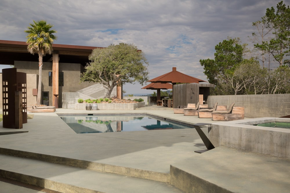 The pool of the grounds is surrounded by concrete walkways fitted with sitting areas and planters that support a large trees. Image courtesy of Toptenrealestatedeals.com.