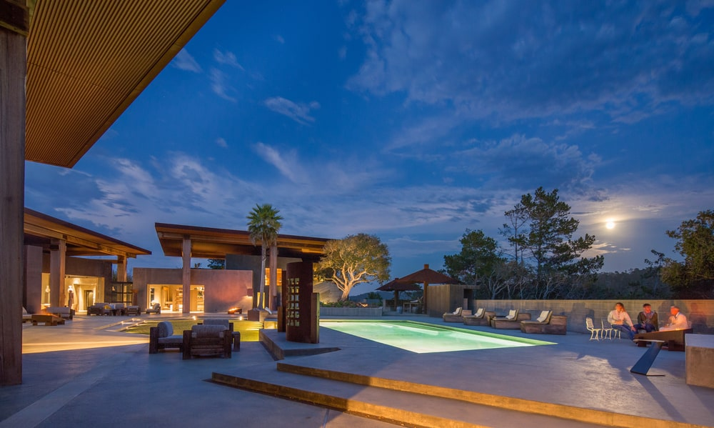 This is a nighttime look at the poolside area. This shows the ethereal glow of the pool and a view of the landscaping that is light with warm yellow lights. Image courtesy of Toptenrealestatedeals.com.