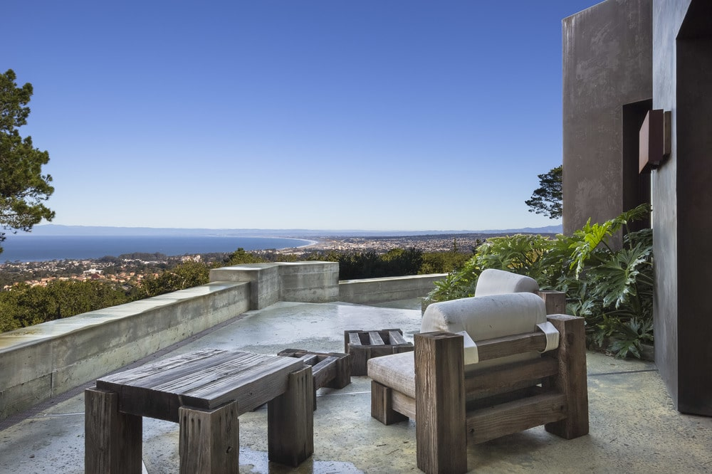 This is the sweeping view of the terrace that is fitted with a wooden outdoor furniture set with cushions. Image courtesy of Toptenrealestatedeals.com.