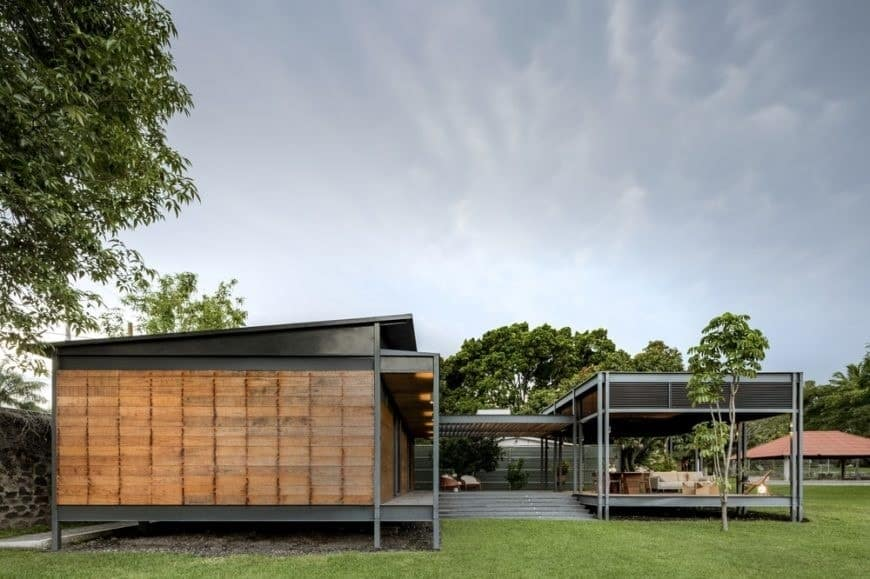 This is a minimalist house with simple steel beams and pillars that support the structure complemented by the simple wooden panels and the grass lawn.