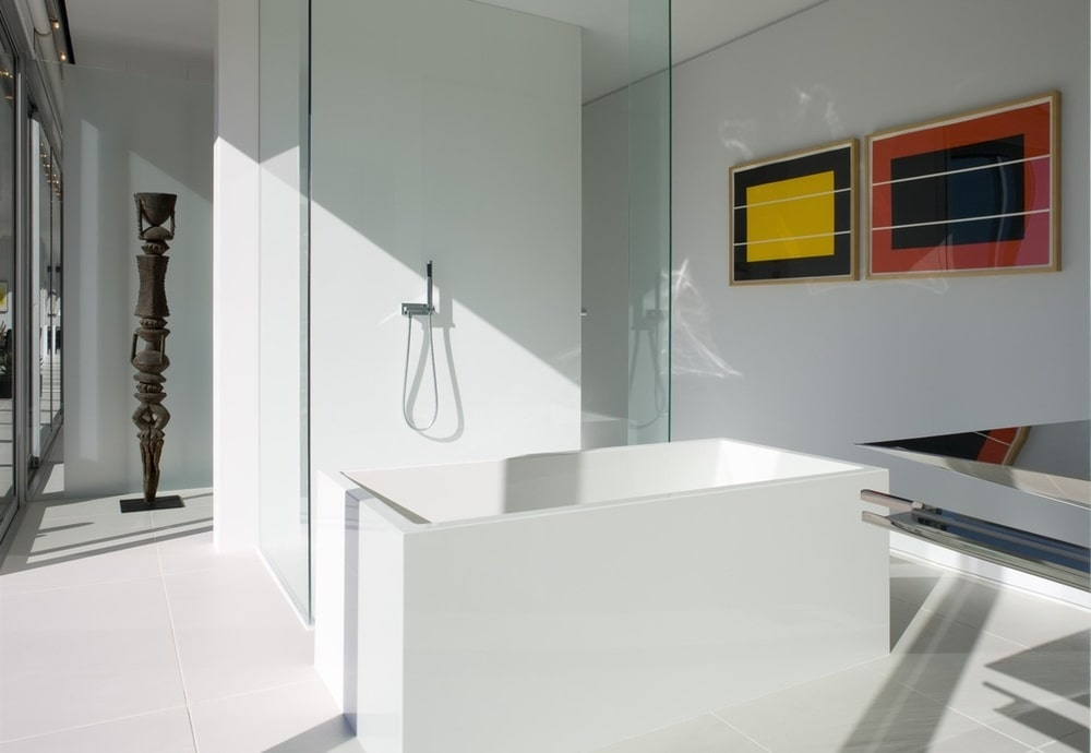 This is the bathroom with a modern white bathtub next to the glass wall of the shower area. Image courtesy of Toptenrealestatedeals.com.