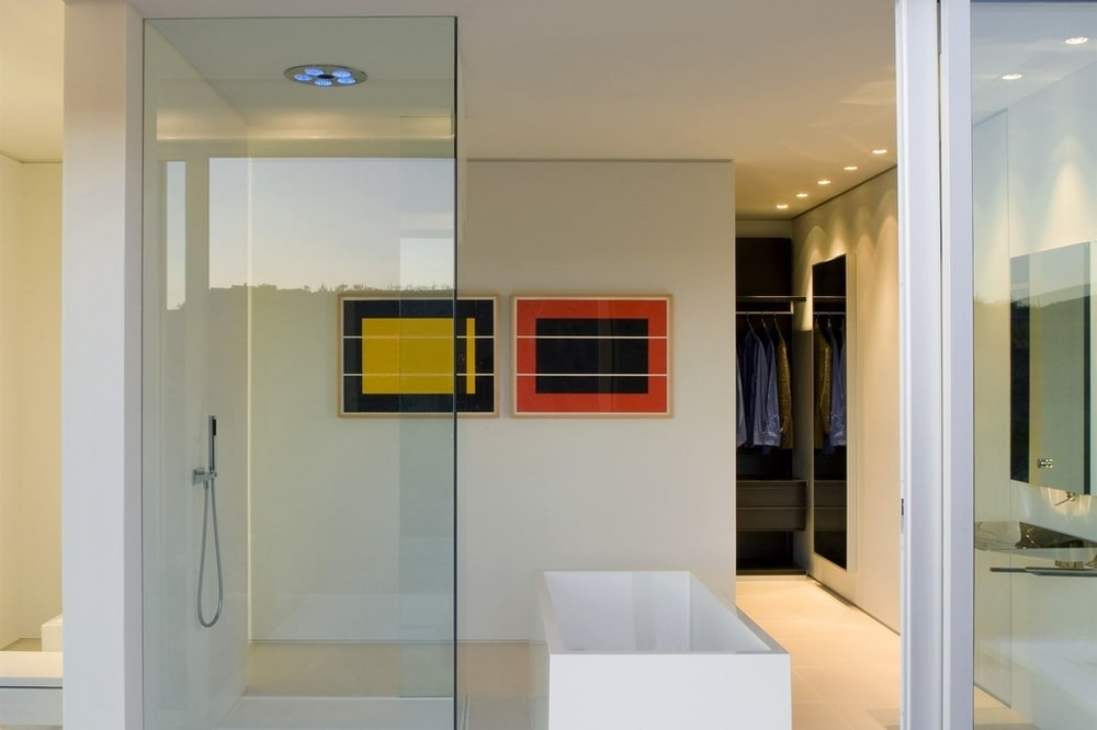 This other look at the bathroom shows the glass wall and the colorful wall-mounted artworks that bring a dash of color to the bright bathroom. Image courtesy of Toptenrealestatedeals.com.