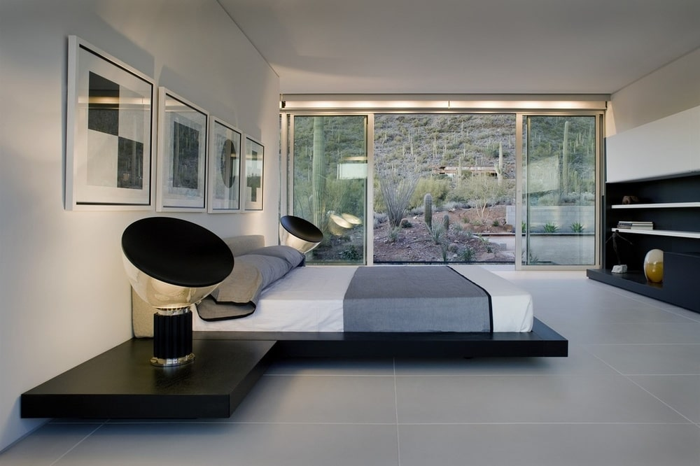 This bedroom has a modern floating platform bed flanked with modern black table lamps that stand out against the white walls. Image courtesy of Toptenrealestatedeals.com.
