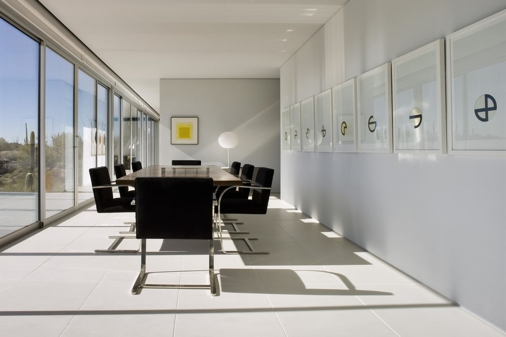 This is a closer look at the dining area a few steps from the living room area. It has a dark dining table surrounded by black chairs to contrast the brightness. Image courtesy of Toptenrealestatedeals.com.