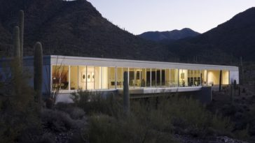 This is a look at the exterior of the house with a long wall of glass that gives a glimpse of the minimalist interiors. This glows from the interior lights making the house stand out against the surrounding desert landscape. Image courtesy of Toptenrealestatedeals.com.