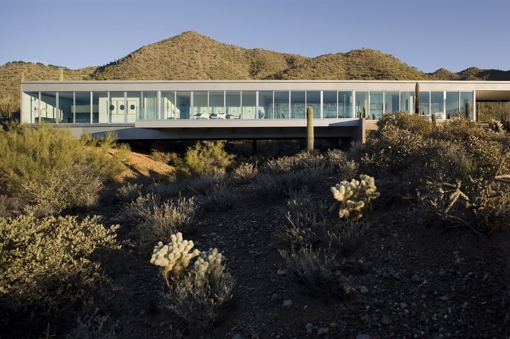 This is an exterior view of the house showcasing the glass walls that show the bright interiors of the house. Image courtesy of Toptenrealestatedeals.com.