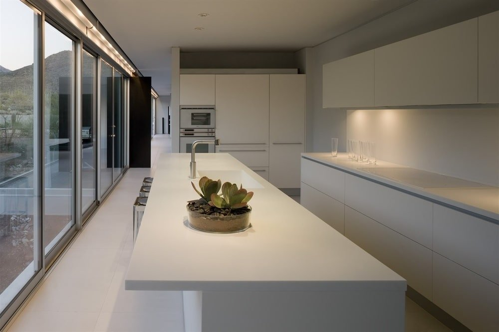 This is the kitchen with bright white cabinetry and countertops. It has a long and narrow design and is brightened by the glass wall on one side. Image courtesy of Toptenrealestatedeals.com.