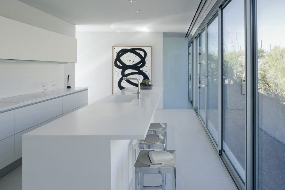 This other view of the kitchen showcases the stainless steel stools paired with the long white breakfast bar adorned with a black and white painting on the far wall. Image courtesy of Toptenrealestatedeals.com.